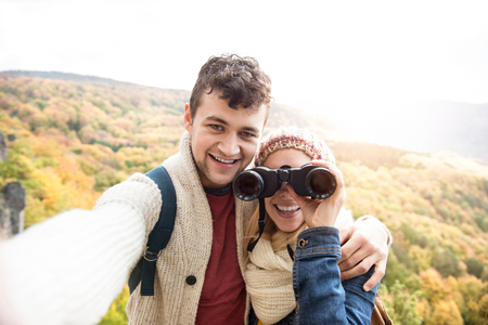 looking through: Beautiful young couple on a walk in sunny autumn forest taking selfie, woman looking through binoculars