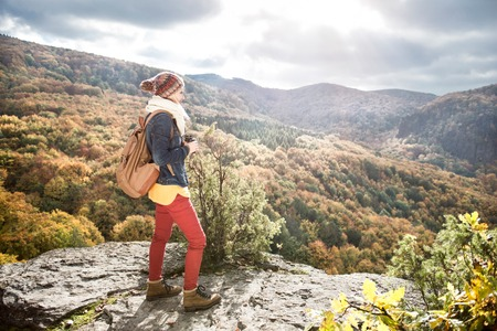hiking shoes: Beautiful woman with backpack, holding binoculars, standing on a rock against colorful autumn forest, rear view
