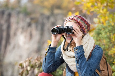 looking through: Beautiful woman looking through binoculars against colorful autumn forest