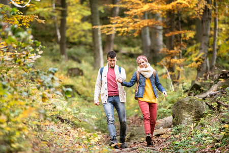 Beautiful couple on a walk in colorful sunny autumn forest. Stock Photo