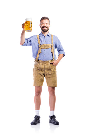 lederhosen: Handsome hipster young man in traditional bavarian clothes holding a mug of beer. Oktoberfest. Studio shot on white background, isolated. Stock Photo