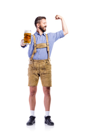 lederhosen: Handsome young man in traditional bavarian clothes, holding a mug o beer, showing biceps on his arms. Oktoberfest. Studio shot on white background, isolated.