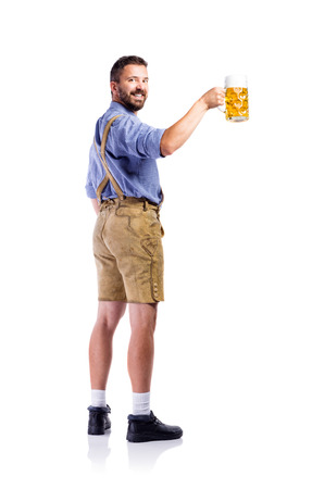 lederhosen: Handsome hipster young man in traditional bavarian clothes holding a mug of beer, rear view. Oktoberfest. Studio shot on white background, isolated. Stock Photo