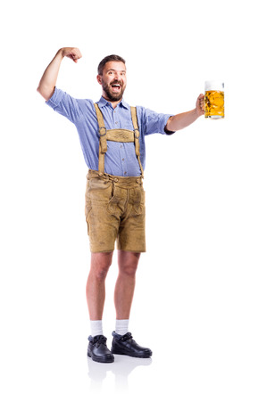 octoberfest: apuesto joven en ropa tradicional de Baviera, que sostiene una taza o cerveza, que muestra el bíceps de los brazos. Oktoberfest. Foto de estudio sobre fondo blanco, aislado.