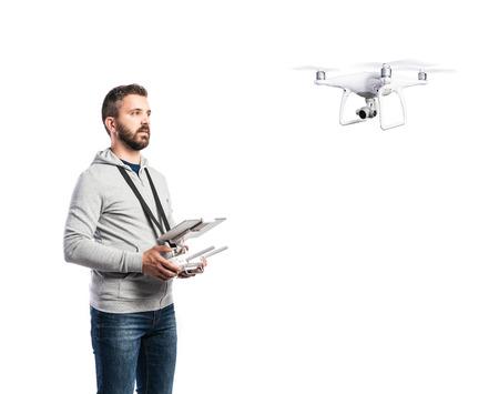 リモート コントロールとカメラで飛行ドローンを持つ男。分離の白い背景で撮影スタジオ。