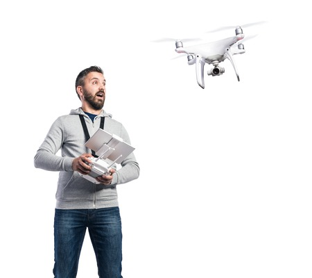 out of control: Man with remote control and flying drone with camera. Studio shot on white background, isolated.