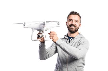 カメラでドローンを保持している灰色のスエット シャツで流行に敏感な若い男。分離の白い背景で撮影スタジオ。