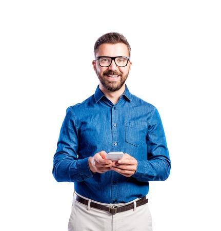 mezclilla: Apuesto joven inconformista en camisa de mezclilla azul, el uso de anteojos negros, sosteniendo el teléfono inteligente, tiro del estudio sobre fondo blanco, aislado