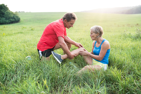 Active senior runners outside in field. Woman with injured knee. Man helping her. Green sunny summer nature. Imagens