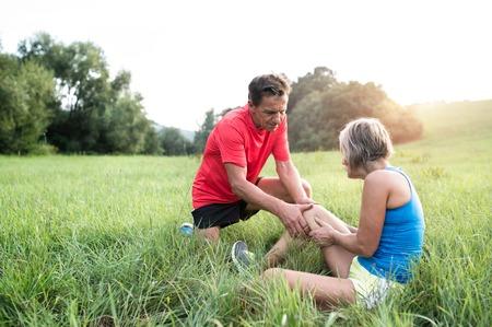 Actieve senior lopers buiten in het veld. Vrouw met gewonde knie. Man haar te helpen. Zonnige groene zomer natuur. Stockfoto