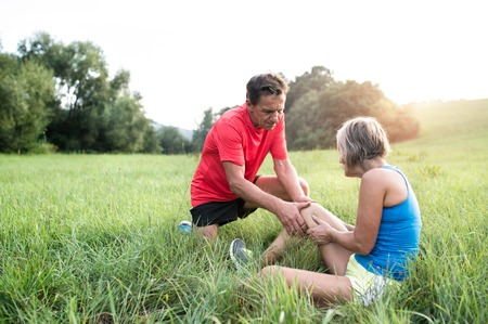 Active senior runners outside in field. Woman with injured knee. Man helping her. Green sunny summer nature. Stock Photo