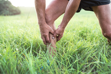 calf pain: Unrecognizable active senior runner outside in field. Man with injured calf. Close up. Green sunny summer nature. Stock Photo