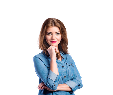 Young beautiful woman in blue denim shirt, holding chin. Studio shot on white background, isolated. photo