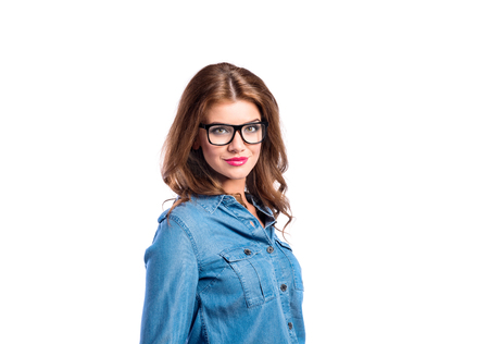 Young beautiful woman in blue denim shirt and trendy black eyeglasses. Studio shot on white background, isolated. photo
