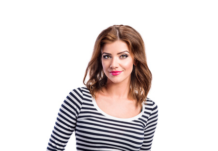 Beautiful young woman in jeans and striped long sleeved t-shirt. Studio shot on white background, isolated. photo