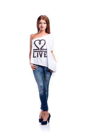 Young beautiful woman in white t-shirt, jeans and heels. Studio shot on white background, isolated. photo
