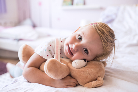 plushie: Cute little girl with her teddy bear at home lying on bed in bedroom