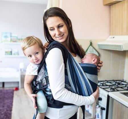 Schöne junge Mutter mit ihrem neugeborenen Sohn in Schlinge und ihre Tochter in Babytrage zu Hause Standard-Bild - 63859444