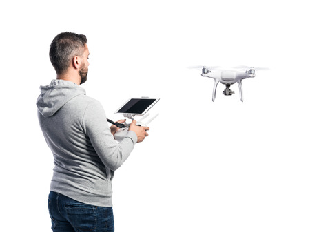 controlling: Man with remote control and flying drone with camera. Studio shot on white background, isolated. Rear view. Stock Photo
