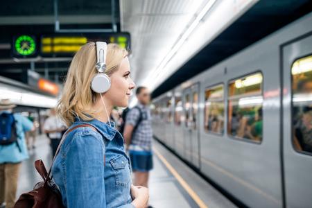 mochila de viaje: Hermosa mujer joven rubia en camisa de mezclilla con auriculares, de pie en la plataforma subterráneo, esperando para entrar en un tren Foto de archivo