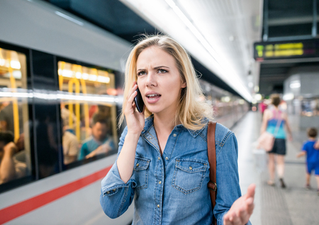waiting phone call: Angry young blond woman in denim shirt with smartphone making phone call. Standing at the underground platform, waiting to enter a train. Stock Photo