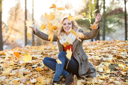 women sitting: Beautiful young woman in checked coat, red sweater and white knitted scarf in autumn park sitting on the ground, throwing yellow tree leaves in the air