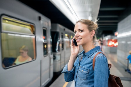 waiting phone call: Beautiful young blond woman in denim shirt with smartphone making phone call. Standing at the underground platform, waiting to enter a train.