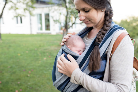 upbringing: Beautiful young mother with her newborn baby son in sling outside in green nature.