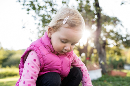 squatting down: Cute little girl in pink sweatshirt and vest outside in nature on a sunny day, squatting down