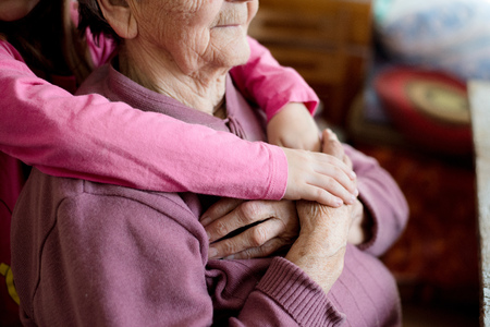 クローズ アップ。認識できない孫娘が祖母の手を繋いでいます。白い木製の背景で撮影スタジオ。