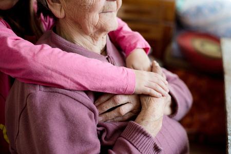 Detailopname. Onherkenbare kleindochter hand in hand van haar grootmoeder. Studio op witte houten achtergrond wordt geschoten die.