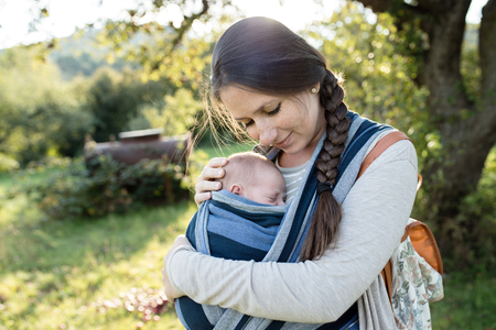 Beautiful young mother with her newborn baby son in sling outside in green nature.