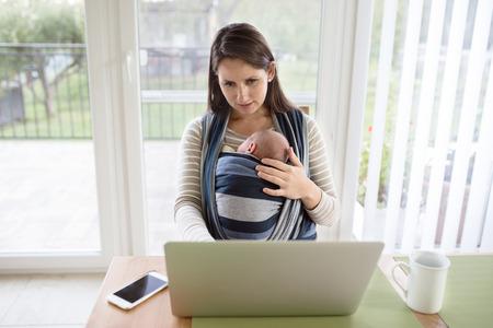 madre trabajando: joven madre hermosa en el país que lleva a su hijo recién nacido en la honda, trabaja en el cuaderno, teléfono inteligente establecidos en la tabla Foto de archivo