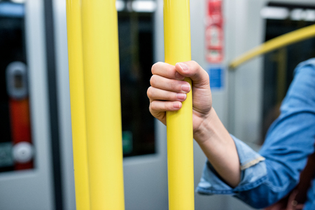 tightly: Close up, hand of unrecognizable woman in denim shirt traveling by subway train, holding yellow handrail tightly Stock Photo
