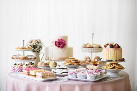 Mesa con un montón de tartas, bizcochos, galletas y cakepops. estudio de disparo. Foto de archivo - 64614738