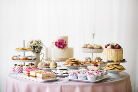 table decoration: Table with loads of cakes, cupcakes, cookies and cakepops. Studio shot. Stock Photo