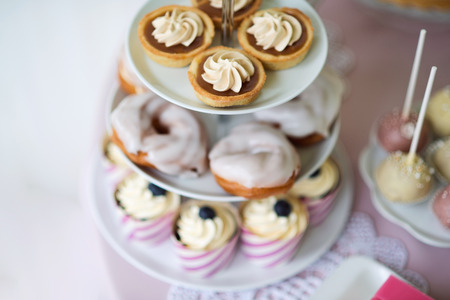 cakestand: Tarts with meringues, glazed cream puffs or profiterole and cupcakes on cakestand. Cake pops on plate.