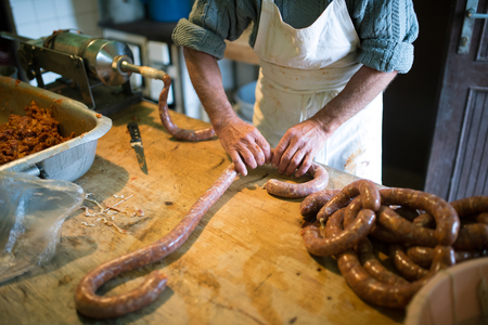 filler: Unrecognizable man making sausages the traditional way using sausage filler. Homemade sausage. Stock Photo
