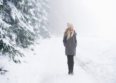 walk in: Beautiful young blonde woman in gray coat on a walk in winter nature. Snowy day.