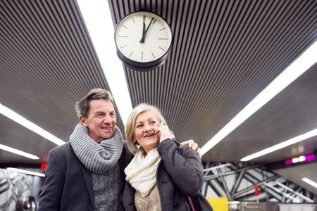 waiting phone call: Beautiful senior couple standing at the underground platform, waiting. Woman with smart phone making phone call. Stock Photo