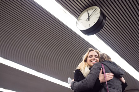 good bye: Two beautiful women, mother and daughter, standing at the underground platform, hugging. Welcoming or saying good bye.