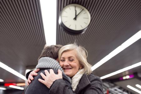 good bye: Beautiful senior couple standing at the underground platform, hugging. Welcoming or saying good bye. Five past twelve. Stock Photo