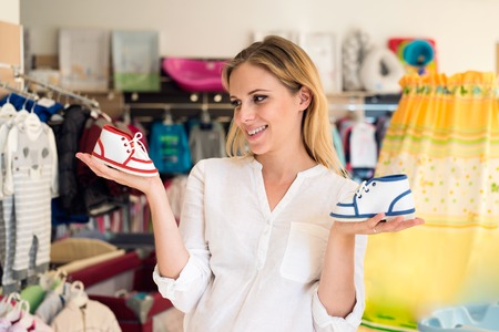 whether: Beautiful pregnant woman in white shirt shopping shoes for her baby, not knowing whether to buy blue for boy or red for girl Stock Photo