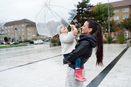 rain boots: Beautiful young mother holding her little daughter under the umbrella in town on a rainy day.