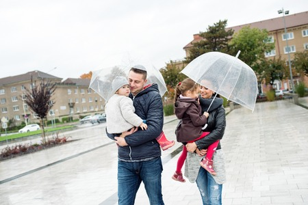 Beautiful young family with two little daughters under the umbrellas, in town on a rainy day. Stock Photo
