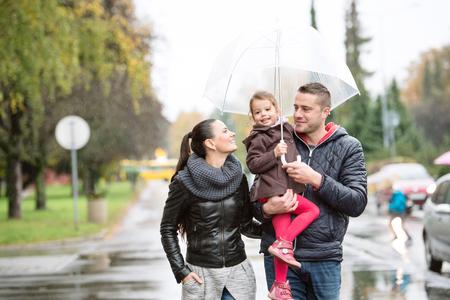 傘の下で娘と美しい若い家族。雨の日に通りを歩いてください。