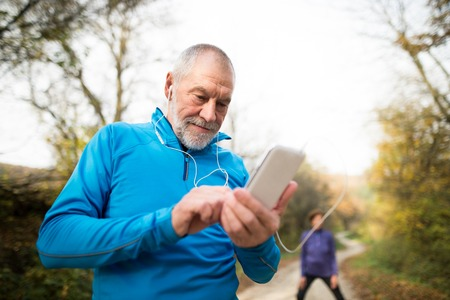 自然の中で上級ランナー ストレッチします。イヤホンでスマート フォンを持つ男。音楽を聴いたり、フィットネス アプリケーションによる携帯電