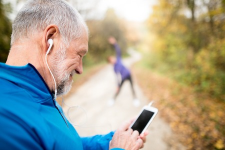 Senior runners in nature, stretching. Man with smart phone with earphones. Listening music or using a fitness app. Using phone app for tracking weight loss progress, running goal or summary of his run. 免版税图像
