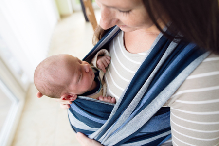 a young baby: Close up, beautiful young mother carrying her newborn baby son in sling at home