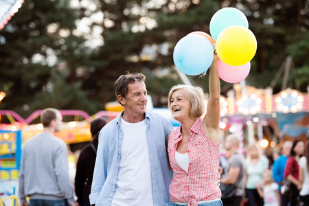 fair woman: Senior couple having a good time at the fun fair. Woman holding colorful balloons. Sunny summer day.